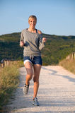 Woman jogging and listening to music Stock Images