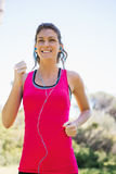Woman jogging while listening to music Royalty Free Stock Photography