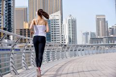 Woman jogging at morning. Running in city park. Woman runner outside jogging at morning with Dubai urban scene in background stock image
