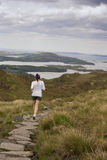 Woman jogging at mountain. Young woman jogging in the mountain track with view to the sea royalty free stock image