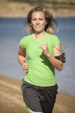Woman jogging with music. A woman jogging down the beach listening to her music Royalty Free Stock Photo