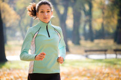 Woman jogging in nature. Young woman jogging in beautiful autumn nature stock photos
