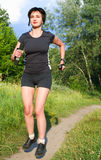 Woman jogging outdoors in forest Stock Photography