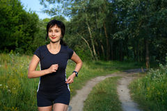 Woman jogging outdoors in forest Royalty Free Stock Images