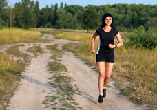 Woman jogging outdoors in summer Stock Images