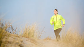 Woman Jogging Over Beach Dunes Stock Photo