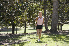 Woman jogging in park, listening to MP3 player, smiling, trees in background Royalty Free Stock Image