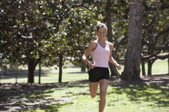 Woman jogging in park, listening to MP3 player, smiling, trees in background Royalty Free Stock Images