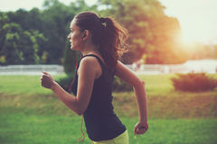 Woman jogging at park. Pretty sporty woman jogging at park in sunrise light stock photo