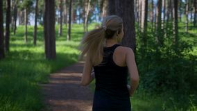 Woman jogging in the park. She switching music on her music player. Technology in sports stock video footage