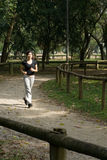 Woman Jogging through Park - Vertical Royalty Free Stock Image