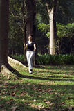 Woman Jogging through Park - Vertical Royalty Free Stock Photo