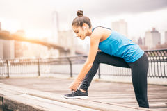 Woman jogging in a park. Young sportive woman getting ready to start running workout - Athlete running outdoors at sunset - Attractive girl making sport to lose Stock Photography