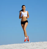 Woman jogging on sand royalty free stock photography
