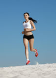 Woman jogging on sand Stock Images