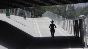 Woman Jogging silhouette Under a Bridge stock video footage
