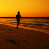 Woman jogging during Sunset over Jumeira beach in Dubai. Royalty Free Stock Photos