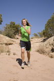 Woman jogging on trail. A woman wearing green jogging down a sandy trail Stock Photography