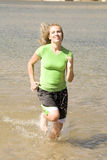 Woman jogging in water. A woman jogging and splashing water Stock Photos