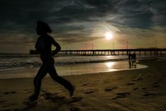 Woman joggs on the beach. A women silhouette is jogging on the beach. It is Sunset. The location is Venice beach Los Angeles Royalty Free Stock Photo