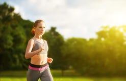 Woman jogs runs on nature Stock Photos