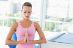 Woman with joined hands and eyes closed at fitness studio Stock Photos