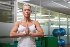 Woman with joined hands and eyes closed at fitness studio Stock Photography