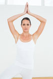 Woman with joined hands over head at a fitness studio Royalty Free Stock Image