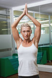 Woman with joined hands over head at fitness studio Royalty Free Stock Photo