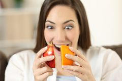 Woman joining half an apple and orange. Sitting on a couch in the living room at home Royalty Free Stock Images