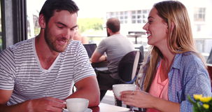 Woman Joins Man Sitting At Table In Coffee Shop. Woman greets man sitting at table in coffee shop before sitting down and joining him.Shot in 4k on Sony FS700 at stock video footage