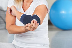 Woman with joint pain in gym. Woman with joint pain and bandage in gym Royalty Free Stock Photo