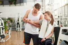 Woman with joint pain in gym. Young muscular trainer touching female injured hand at fitness club. Sprained wrist injury. Exercises for wrist strain stock images