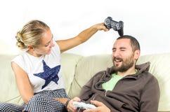 Woman joke hits man with joypad controller Stock Image
