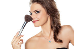 Woman joking with a make-up brush Royalty Free Stock Images