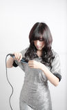 Woman joyful with her hair straightener Stock Images