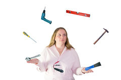 Woman juggles with tool Royalty Free Stock Photography