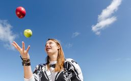 Woman juggling with apples Stock Images