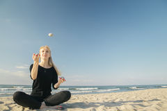 Woman juggling pebbles. Blond woman juggling pebbles at sunny sea beach Royalty Free Stock Images