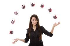 Woman juggling. Young woman juggling a alarm clock Royalty Free Stock Image