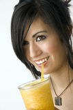 Woman sipping orange juice drinking smiling Royalty Free Stock Photos