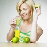 Woman with juice. Woman with a glass of juice and limes Stock Photography