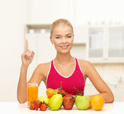 Woman with juice and fruits holding finger up stock photos