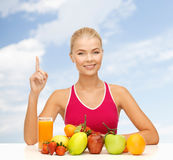 Woman with juice and fruits holding finger up Stock Images