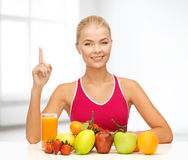 Woman with juice and fruits holding finger up Royalty Free Stock Image