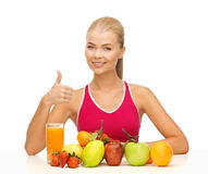 Woman with juice and fruits showing thumbs up Royalty Free Stock Photos