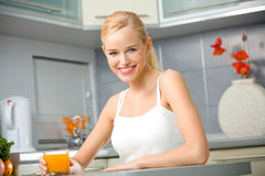 Woman with juice at kitchen Royalty Free Stock Images