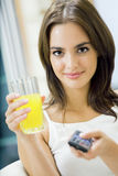 Woman with juice, watching TV Stock Photos