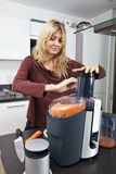 Woman juicing carrots at kitchen counter Royalty Free Stock Images