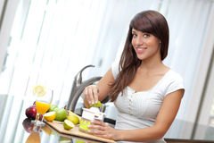 Woman juicing lime. An attractive young brunette woman juicing fruit Stock Photos